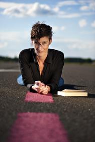Tania Witte auf dem Bauch liegend, Oberkörper aufgestützt, nach vorne schauend mit Buch neben sich